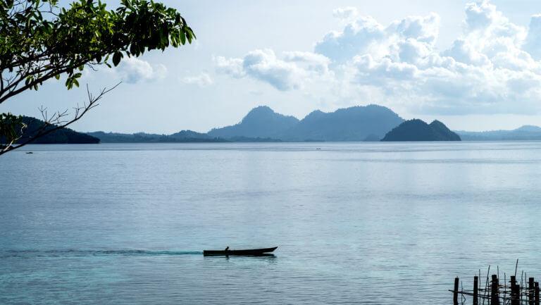 Pescador en barco en las aguas de las islas Togean de Sulawesi