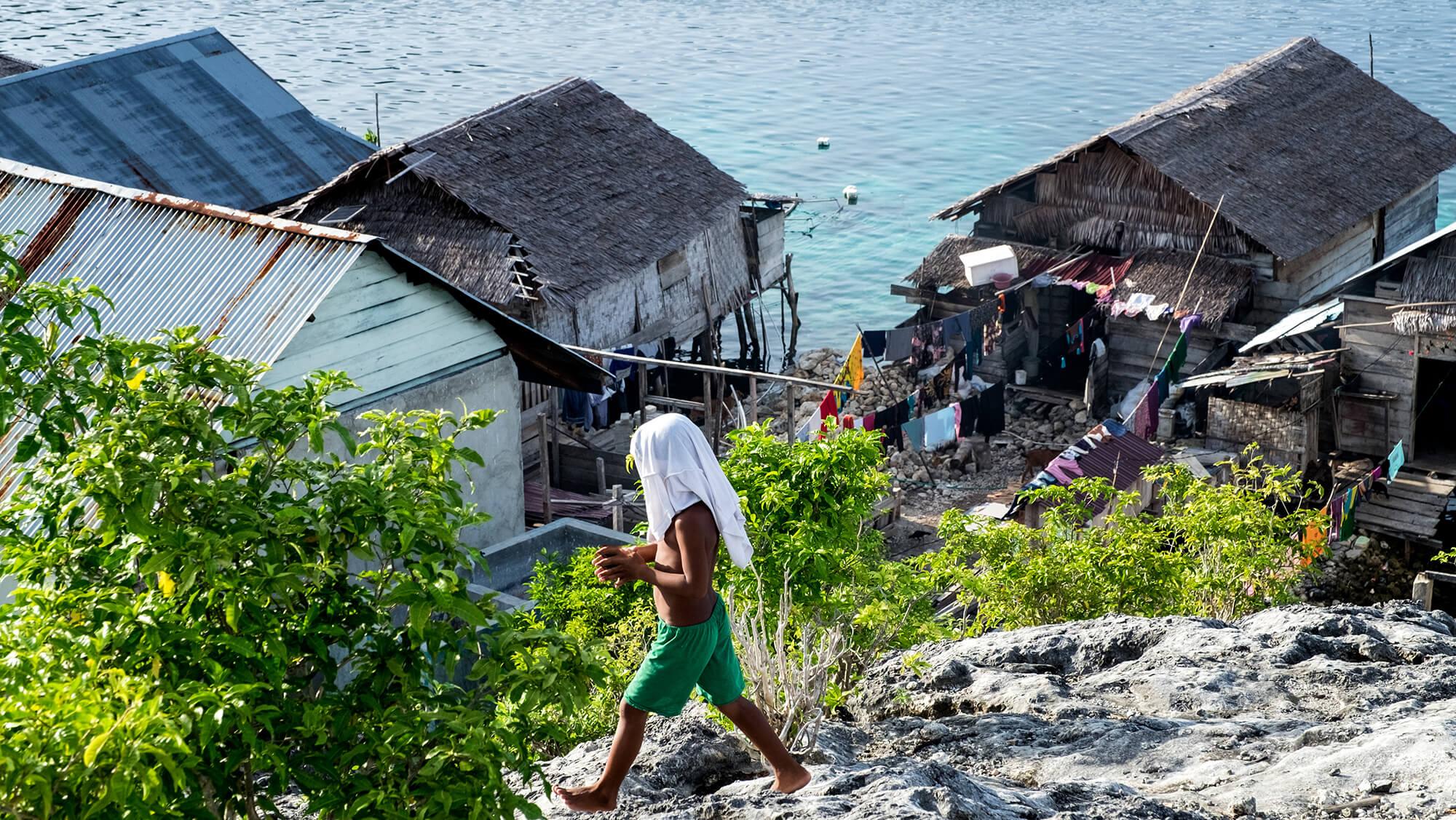 Niño caminando en la aldea bajau de las islas Togean en Sulawesi