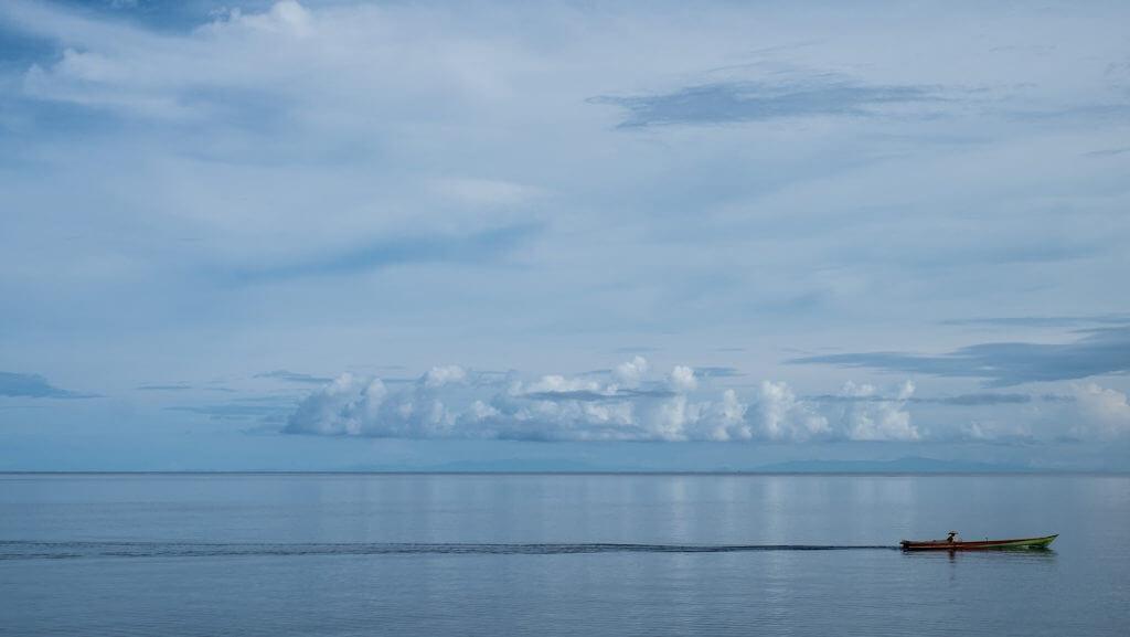 Espejo en el agua con barco navegando en las islas Togean