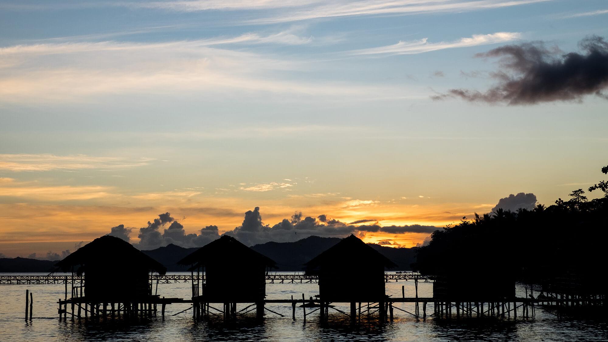 Atardecer en Raja Ampat con cabañas sobre el agua de Papúa