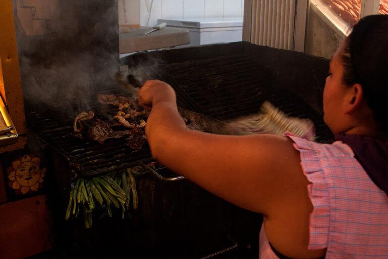Mujer asando maíz y otros productos en un mercado mexicano