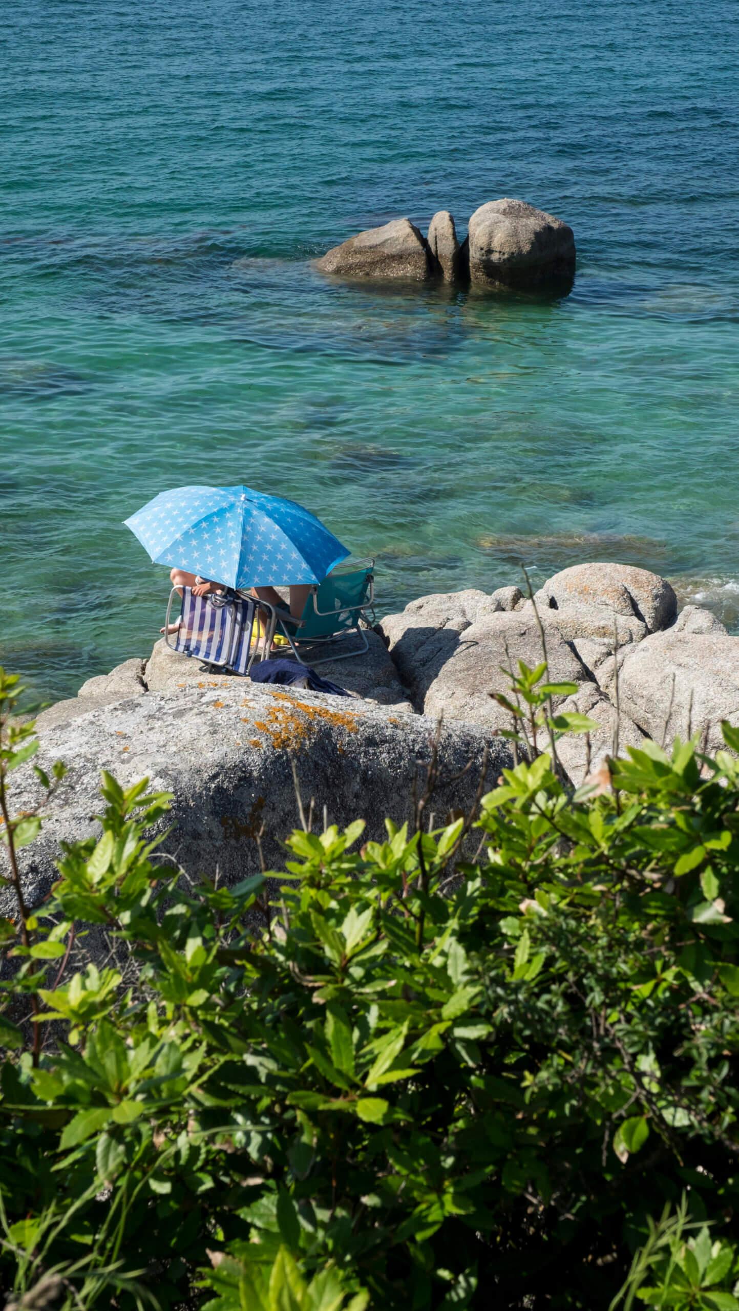 O grove en Pontevedra tomando el sol con sombrilla en las rocas